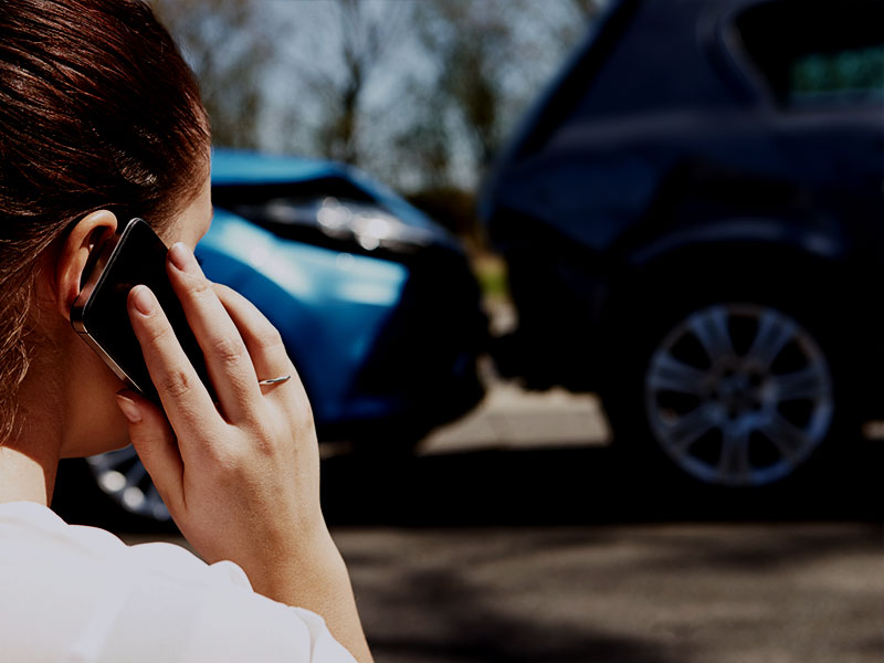 A woman on her cell phone with two crashed vehicles in the background