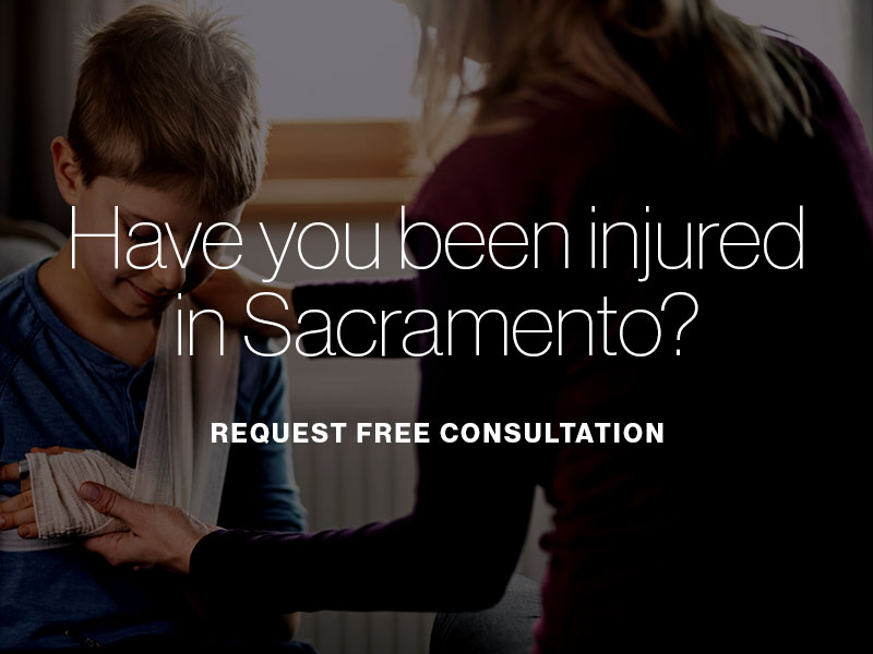 "A mother comforting her son with a broken arm with the text ""Have you been injured in Sacramento? Request free consultation"" superimposed"