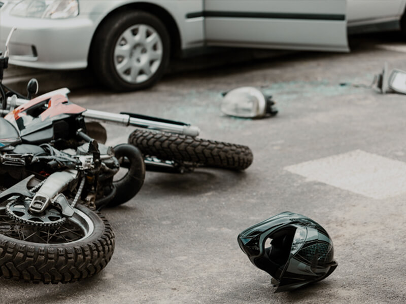 A crashed motorcycle near a car